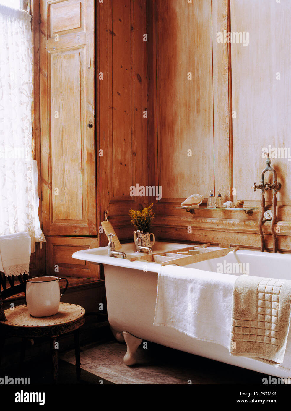 Wooden panelling and clawfoot bath in tradtional country bathroom ...