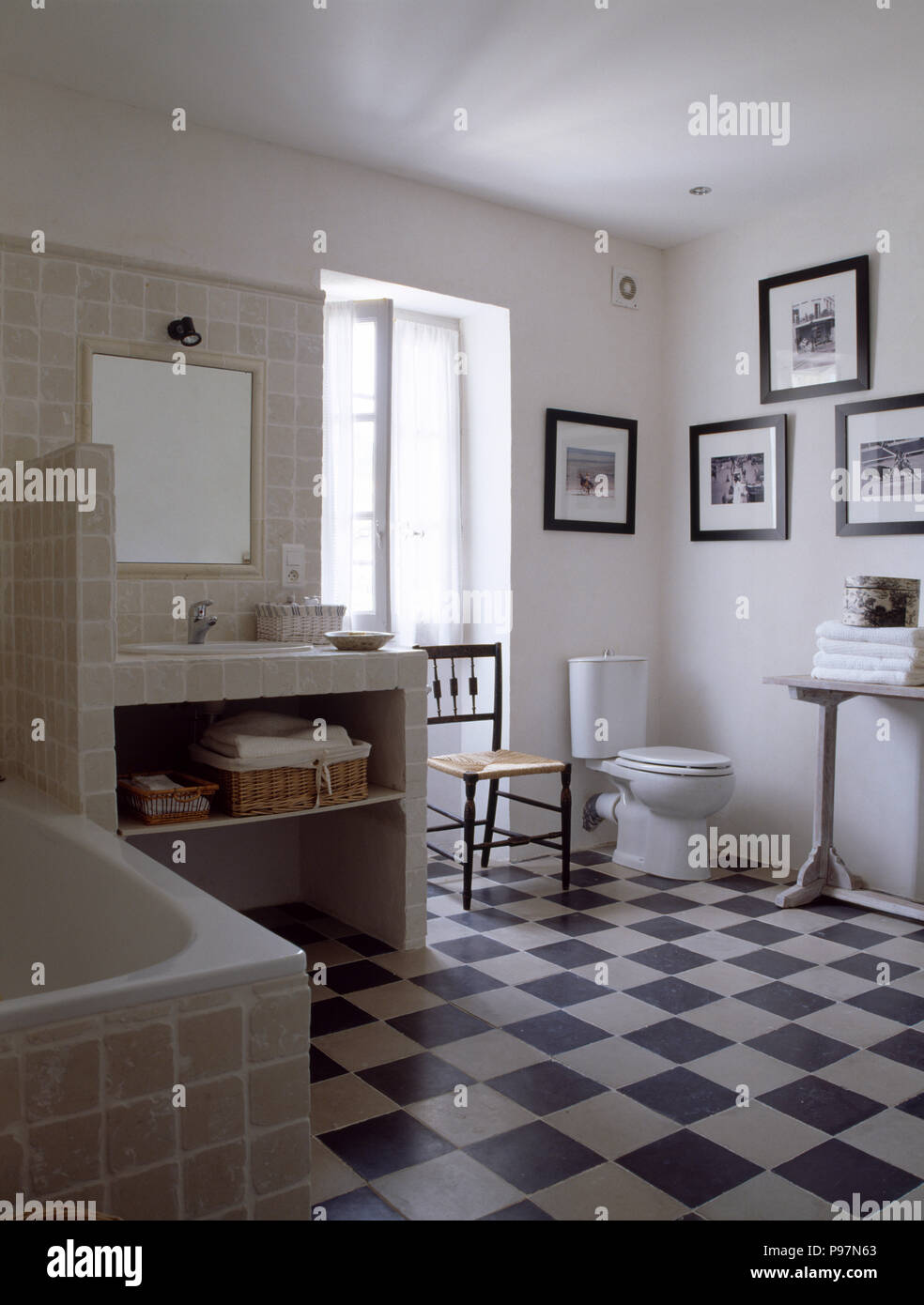 Black+white chequerboard floor in white Provencal bathroom with modern tiled vanity unit - Stock Image
