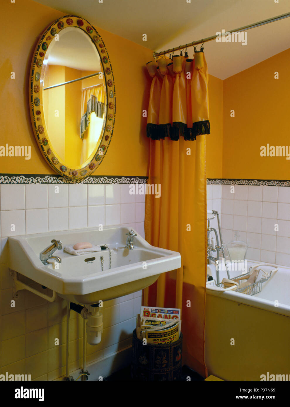 Oval Mirror Above Basin In A Bright Yellow Nineties Bathroom With Shower Curtain On The Bath