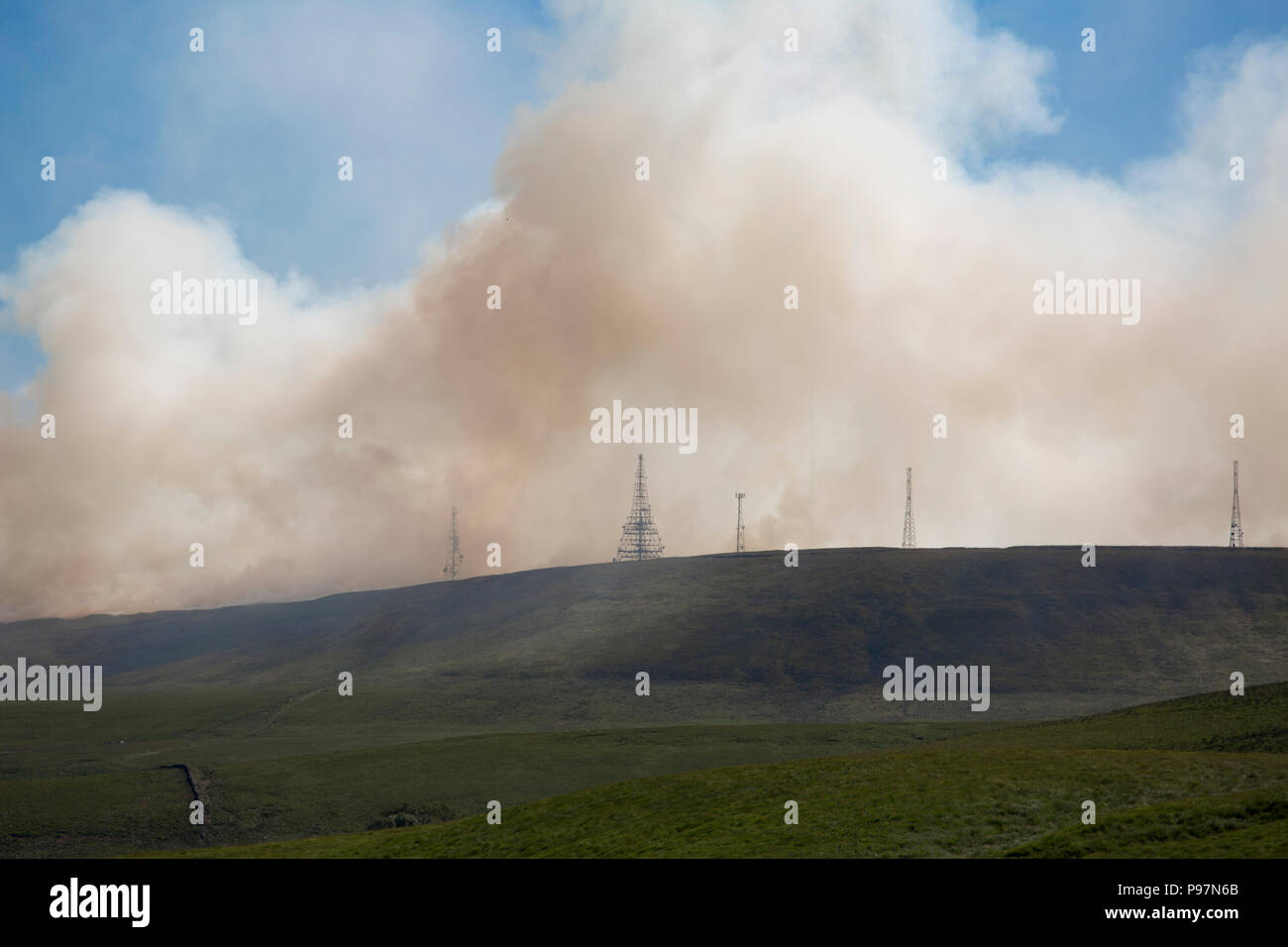 Winter Hill Lancashire on fire with the masts wreathed in smoke. 20th June, 2018. - Stock Image