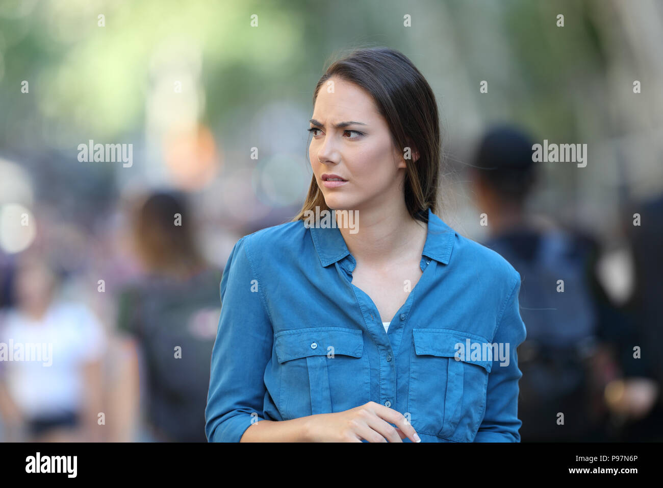 Anxious woman walking on the street looking at side - Stock Image