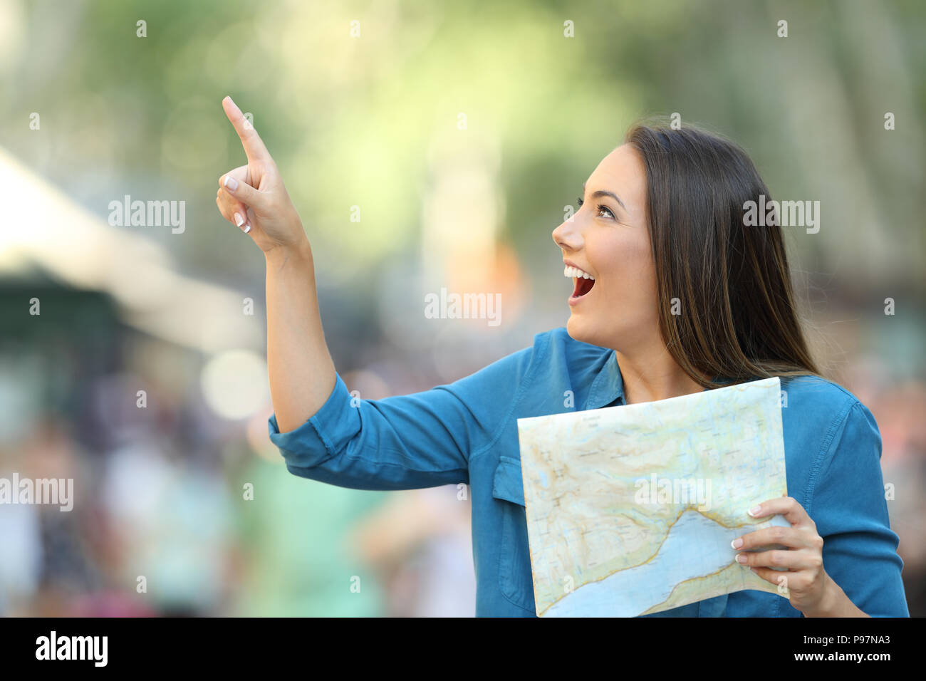 Happy tourist holding a guide and pointing at side on the street - Stock Image