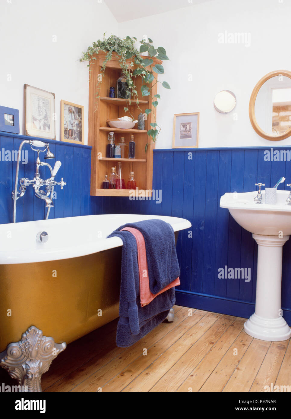 Wooden Flooring And Gold Clawfoot Bath In Traditional Bathroom With