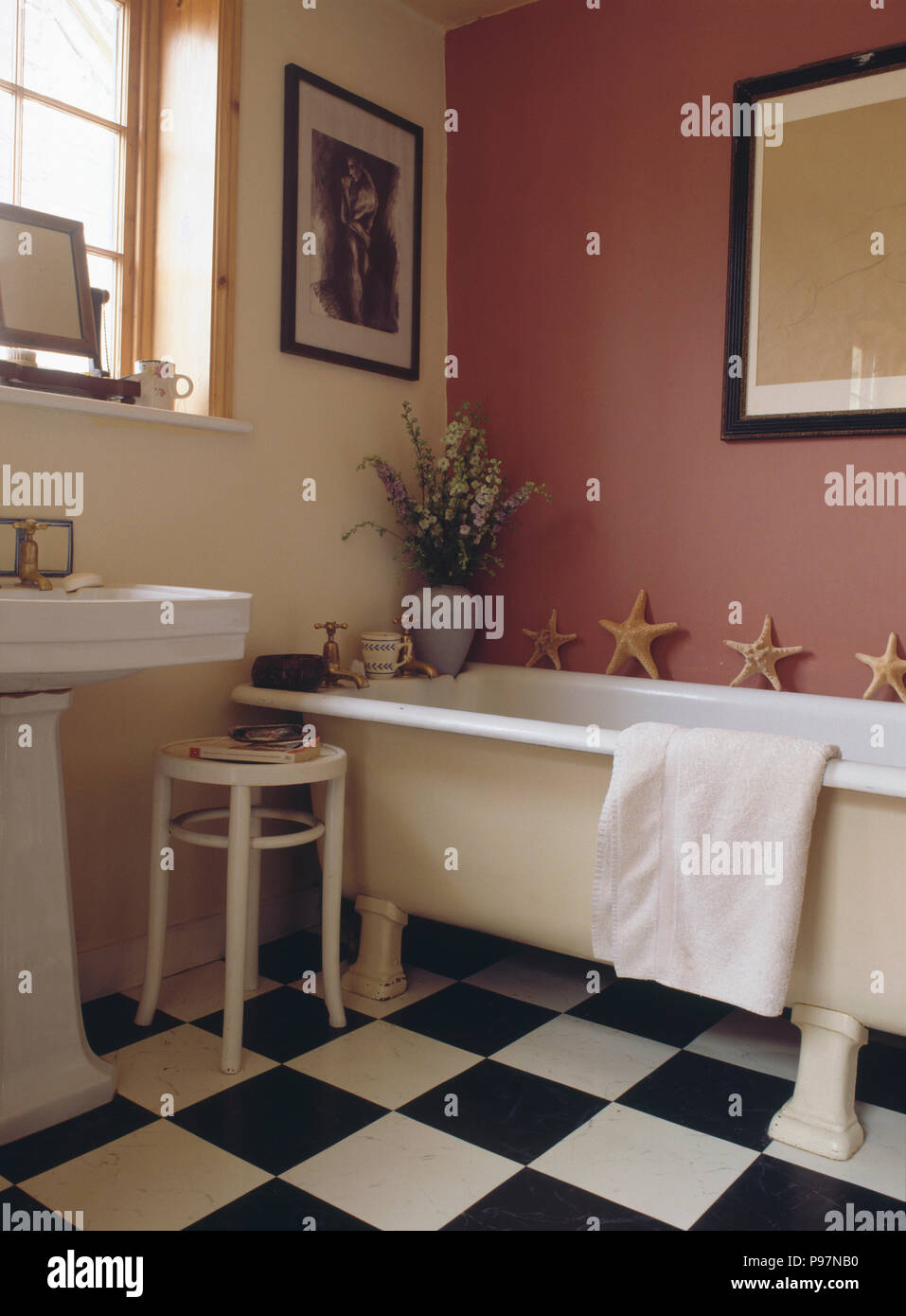 Black And White Chequerboard Vinyl Flooring In Pink Bathroom With Rolltop Bath Stock Photo Alamy