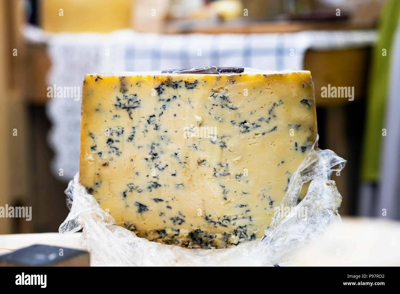 Large cheese wheel with blue mold on market counter, colorful colors. Gastronomic dainty products on market counter, real scene in food market - Stock Image