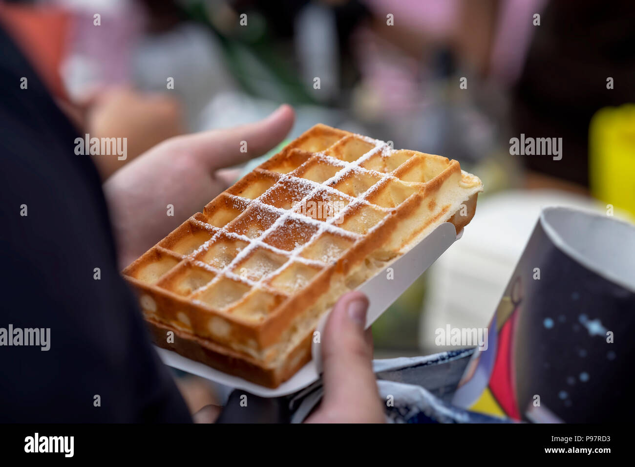 Belgian fresh warm waffle with powdered sugar in hands of buyer. Gastronomic dainty products on market counter, real scene in food market - Stock Image