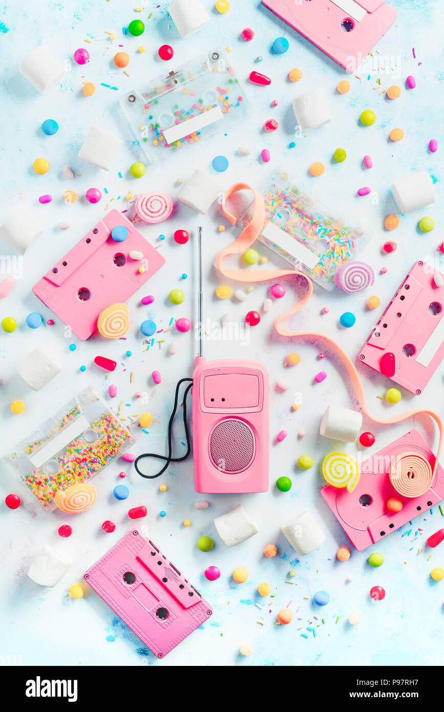 Cassette tapes and retro radio player in a pastel colour flat lay with candies, bonbons, marmalade and bubble gum. Sweet music concept with copy space. Vanilla palette Stock Photo