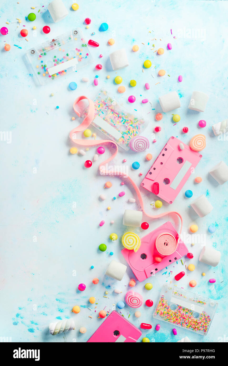 Pink cassette tapes in a sweet sounds concept. Candies, sprinkles and marmalades on a light background with copy space. Pastel color flat lay - Stock Image