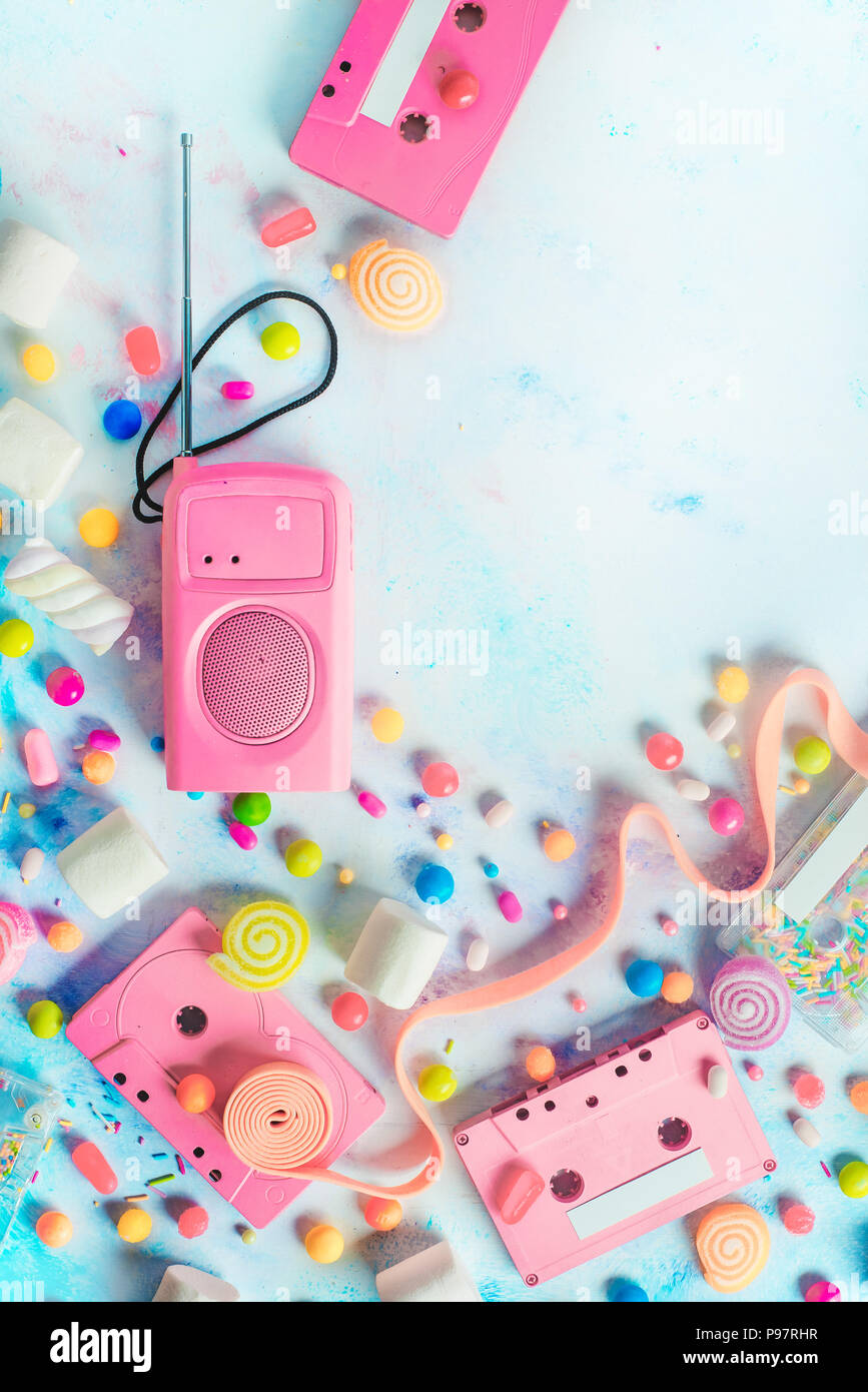 Candy cassette tapes in a pleasant music concept. Candies, sprinkles and marmalades on a light background with copy space. Pastel color flat lay - Stock Image