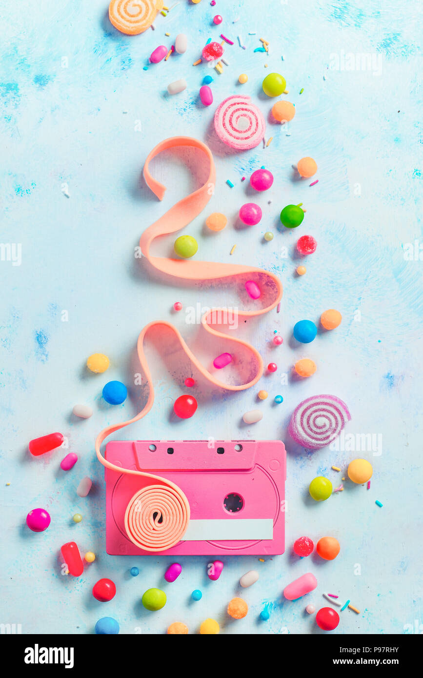 Pink cassette tape with a tape of bubble gum in a gentle and sweet music concept with copy space. Candies, sprinkles, and marmalades in a pastel color flat lay with sweets - Stock Image