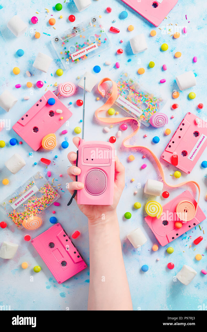 Candy cassette tapes and pink retro radio player in a hand. Candies, sprinkles and marmalades in a pleasant music concept with copy space. Pastel color flat lay with sweets - Stock Image