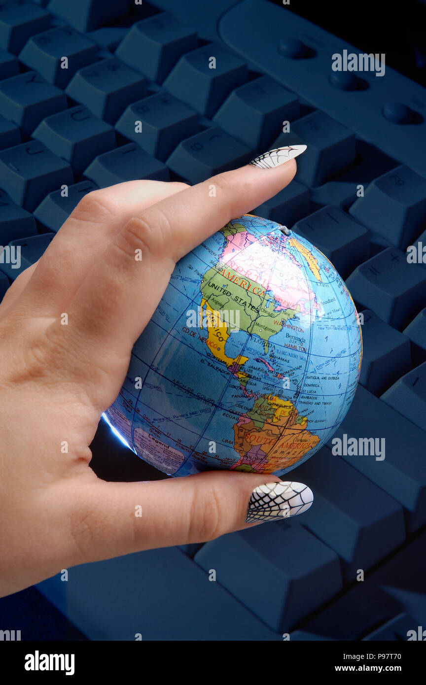 Woman's hand holding the globe, web print fingernails represent world wide web: concepts: connectivity, women in tech, computers, global, etc - Stock Image