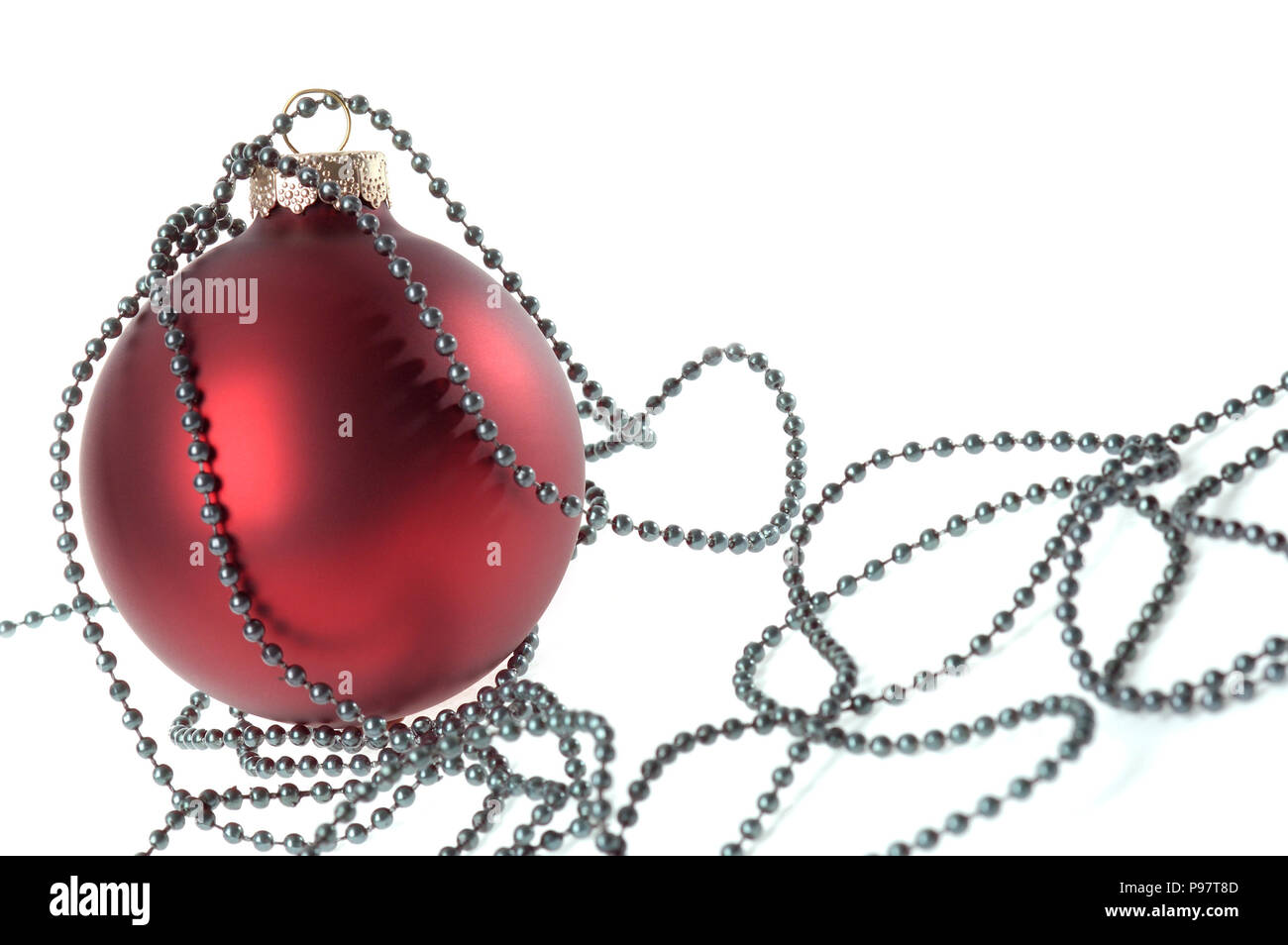 Red Christmas ornament and green beads, decoration - Stock Image