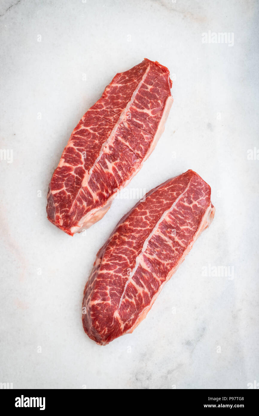 Raw fresh meat Top Blade steaks on light background. top view - Stock Image