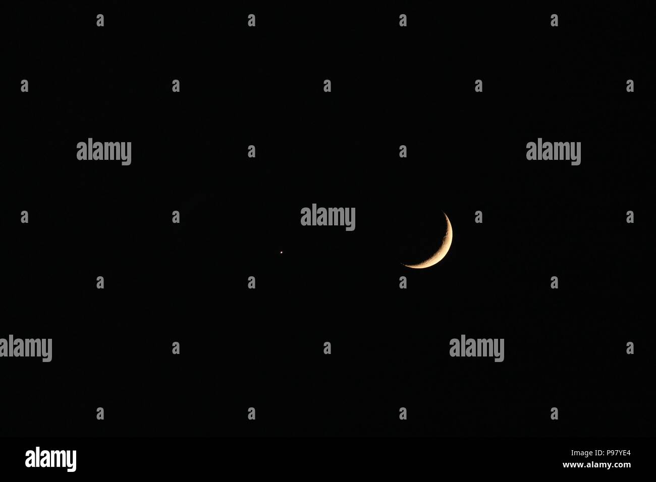 Crescent moon and Mars against black sky Stock Photo