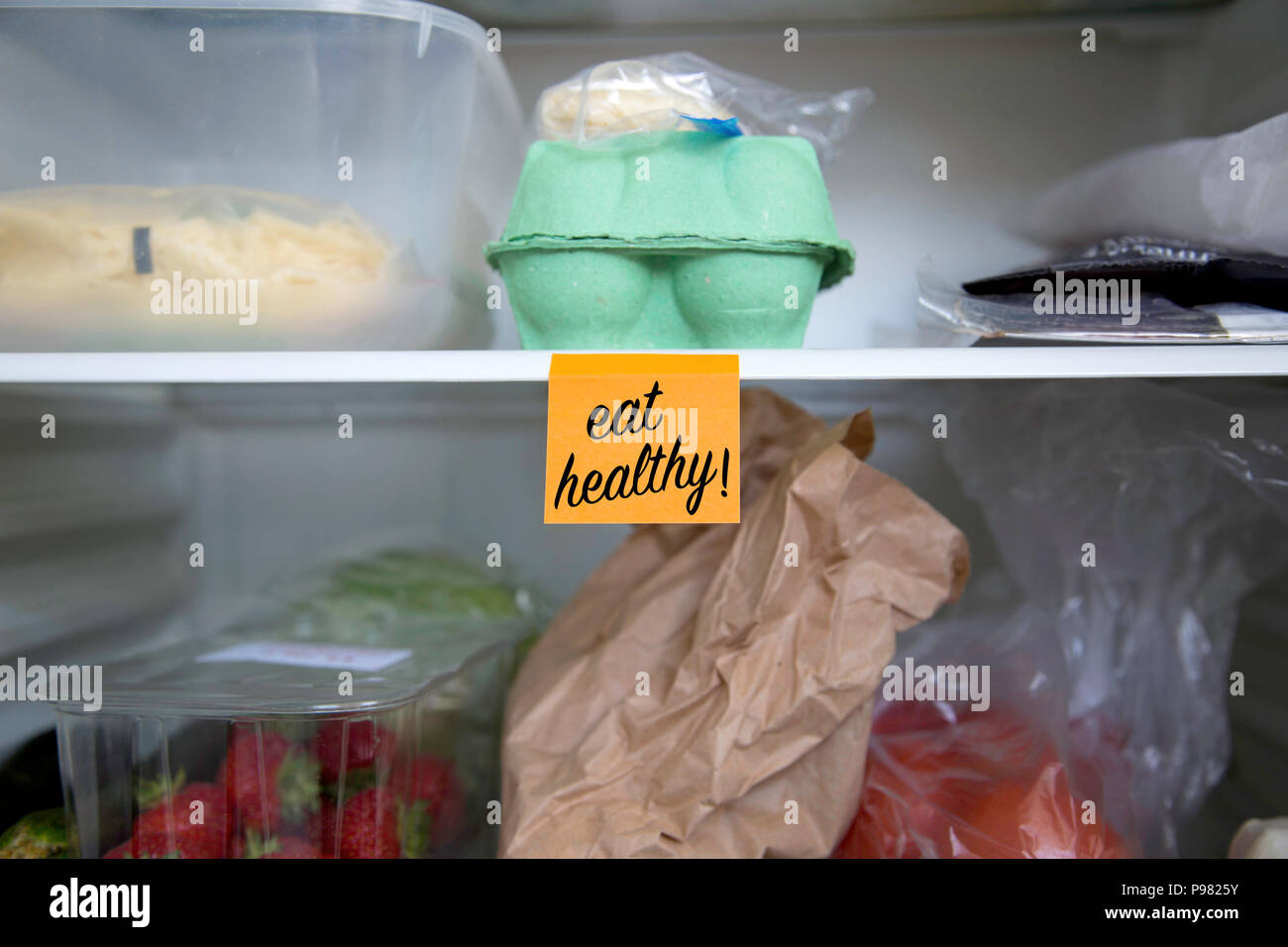 Eat healthy written on a post it note stuck on a fridge shelf with food - Stock Image