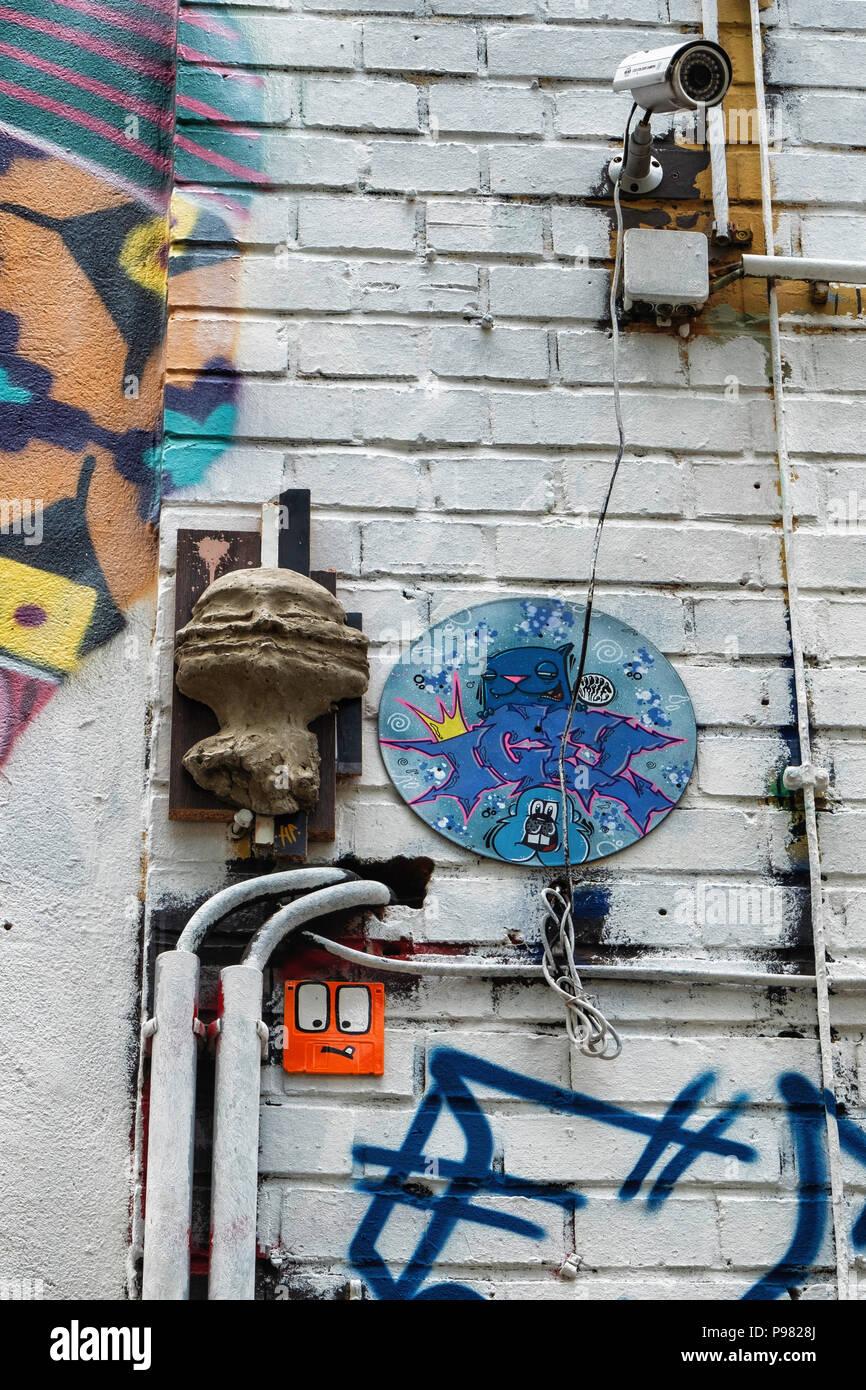 Berlin, Friedrichshain, RAW Gelände. CCTV surveillance camera, street art and old electrical wiring on exterior of old industrial building - Stock Image