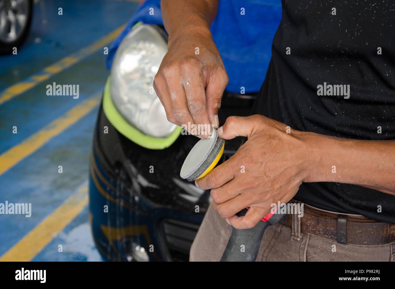 Man holds a polisher car headlights - Stock Image