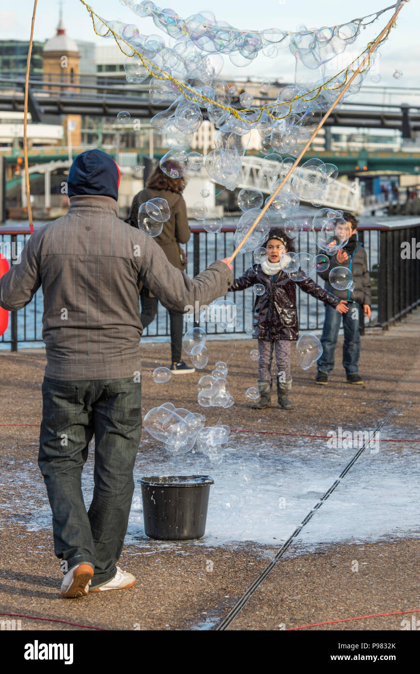 A street entertainer making bubbles to entertain the public on the Southbank in London, England, UK. - Stock Image