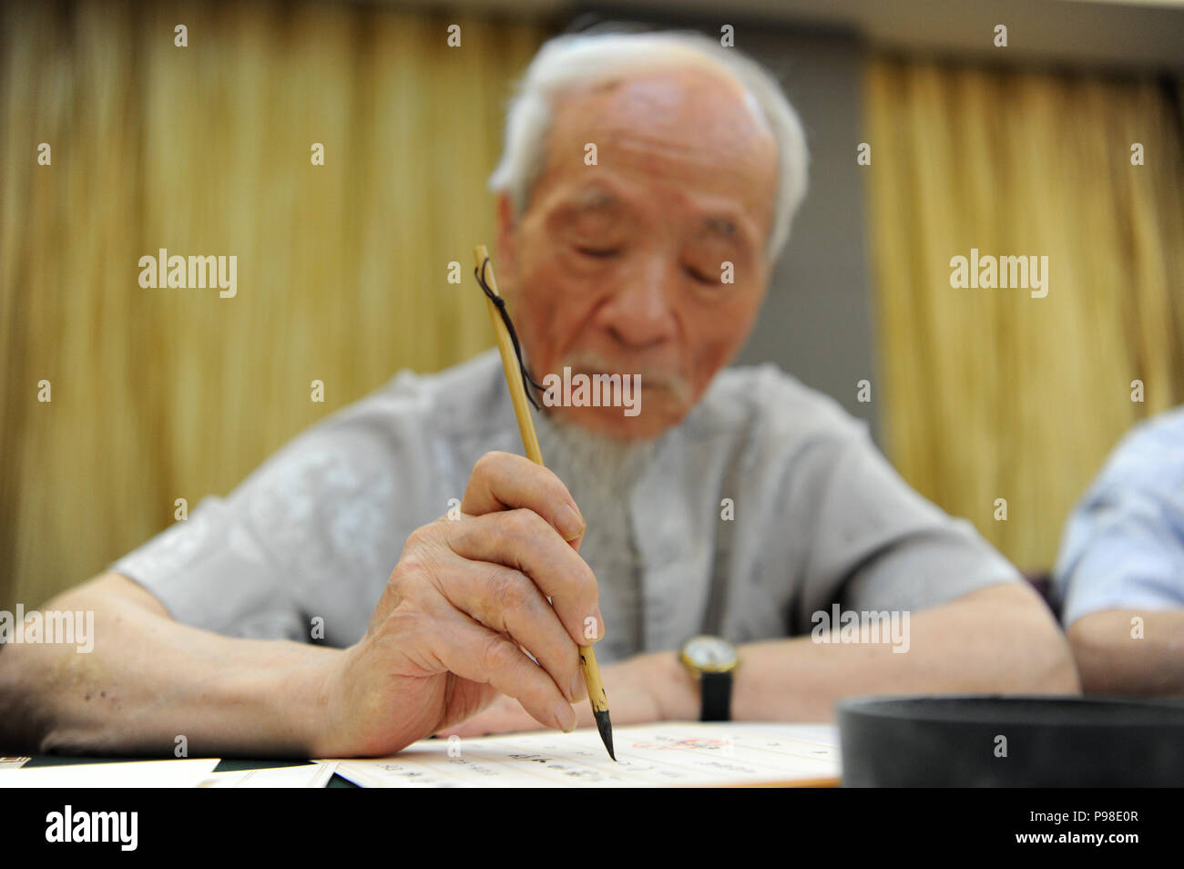 Xi'an, China's Shaanxi Province. 16th July, 2018. Wu Yaohui, a retired teacher from Shaanxi Normal University, writes an admission letter with Chinese writing brush in Xi'an, northwest China's Shaanxi Province, July 16, 2018. Around 4,500 admission letters written by representatives of alumni and retired teachers from Shaanxi Normal University will be delivered to freshmen. The hand-written admission letter has become a feature of Shaanxi Normal University since 2007 Credit: Zhang Bowen/Xinhua/Alamy Live News - Stock Image