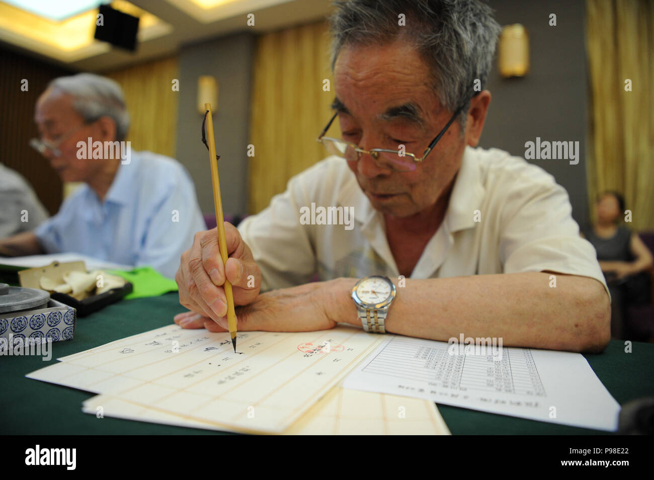 Xi'an, China's Shaanxi Province. 16th July, 2018. Yang Mingtang, a retired teacher from Shaanxi Normal University, writes an admission letter with Chinese writing brush in Xi'an, northwest China's Shaanxi Province, July 16, 2018. Around 4,500 admission letters written by representatives of alumni and retired teachers from Shaanxi Normal University will be delivered to freshmen. The hand-written admission letter has become a feature of Shaanxi Normal University since 2007 Credit: Zhang Bowen/Xinhua/Alamy Live News - Stock Image