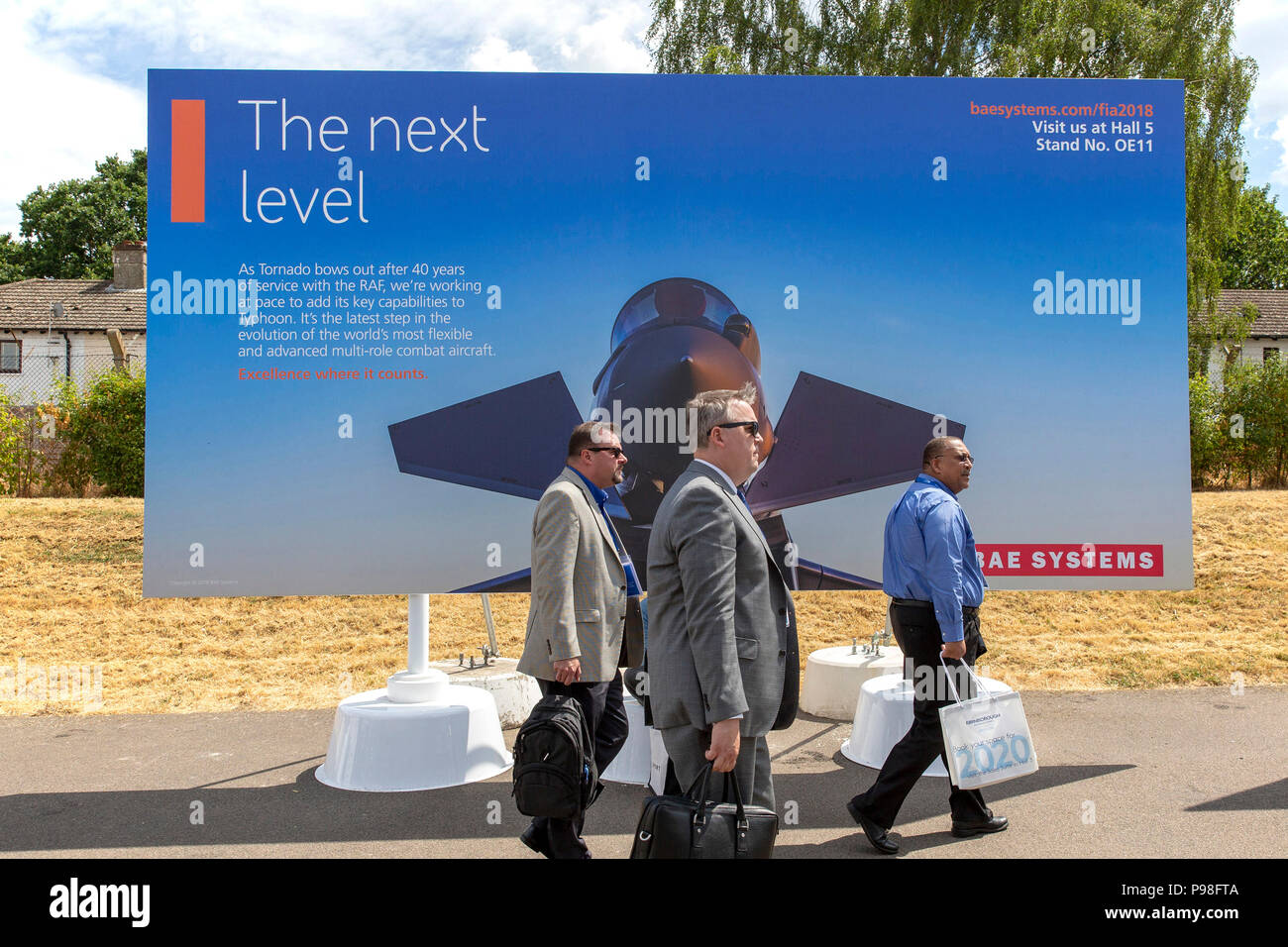 Farnborough Airshow 2018 17th July Three Men Walk Past A BAE Systems Advertisement Hoarding At Trade Day