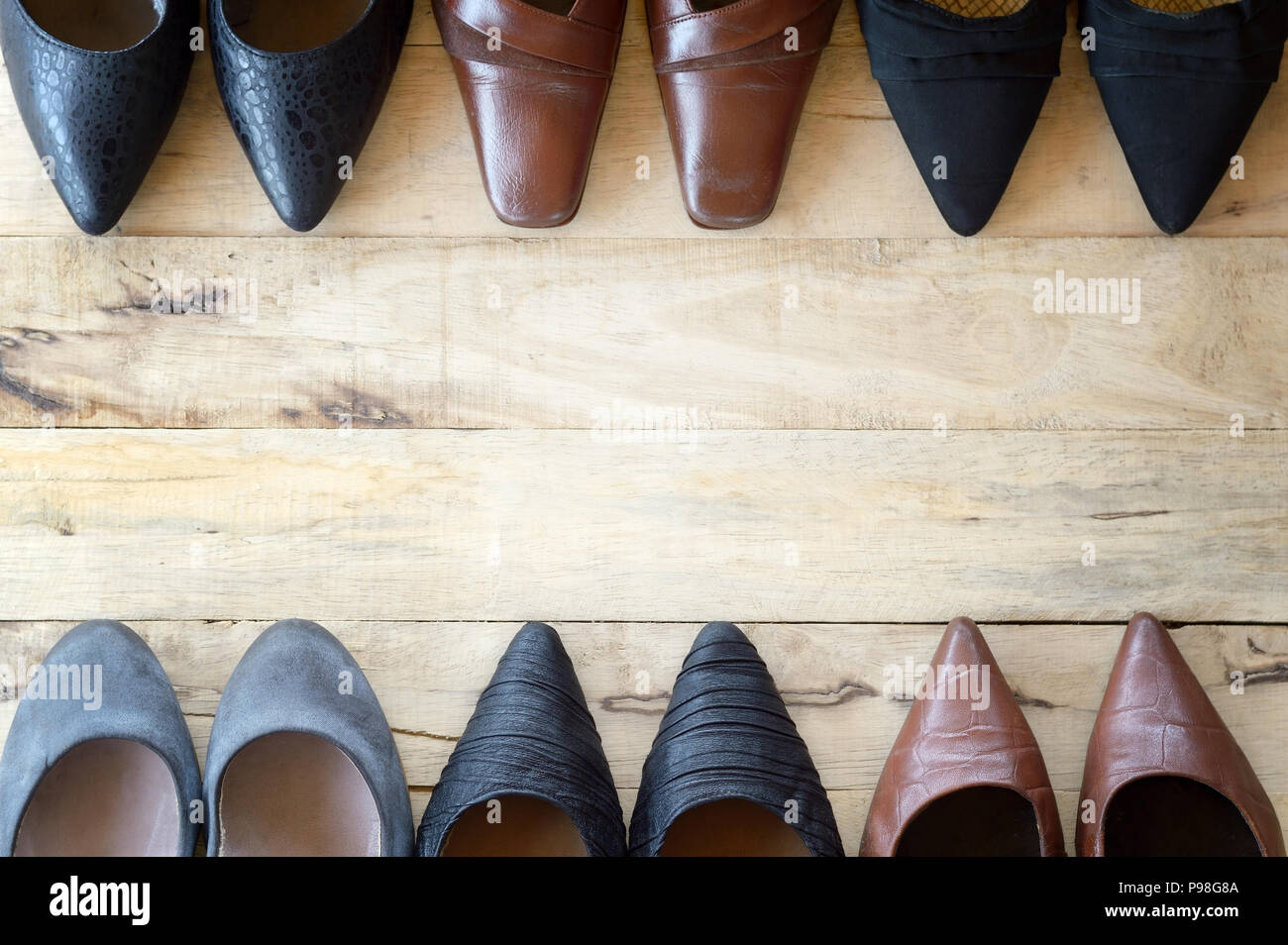 top view of different woman shoe on wooden background, several types of high heels - Stock Image