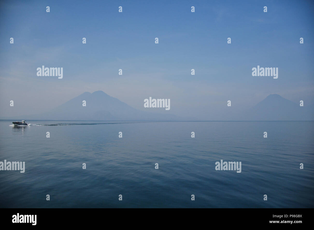 Lake Atitlan in early morning haze with san pedro volcano and Atitlan Volcano in the background with a boat aproaching - Stock Image