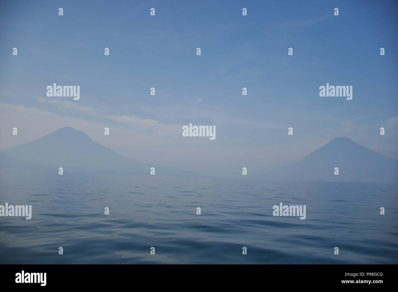 Lake Atitlan in early morning haze with san pedro volcano and Atitlan Volcano in the background - Stock Image