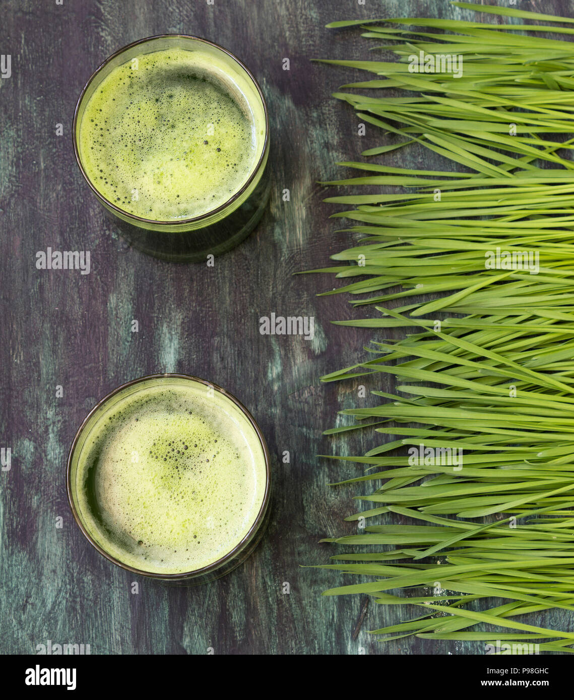 Wheatgrass and glass of green juice- overhead shot - Stock Image