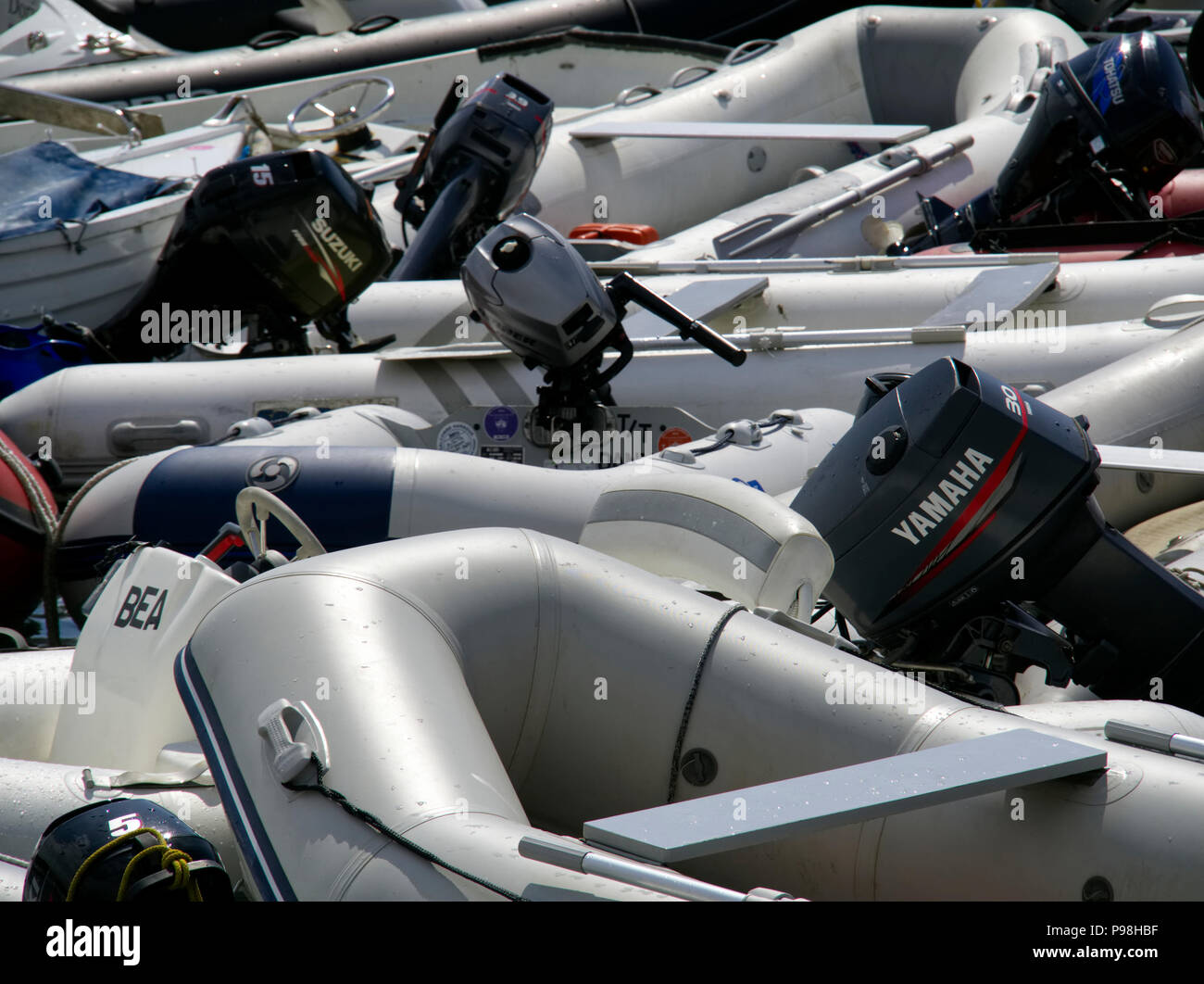 A jumble of RIBs, Rigid Inflatable Boats, with large outboard motors being used as hire boats in Salcombe, Devon. - Stock Image