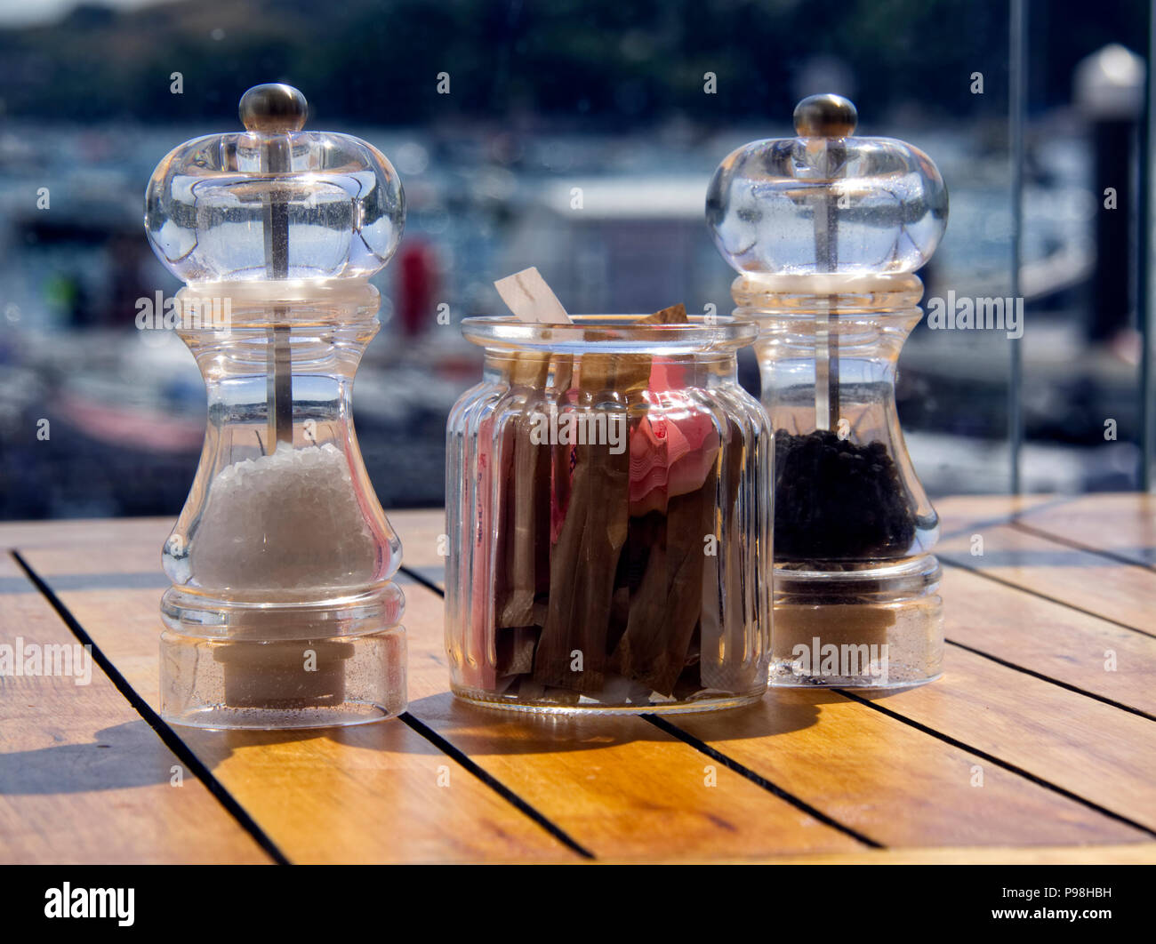 Salt and pepper mills together with a jar containing sugar sachets stand on the table in a harbour-side cafe. - Stock Image