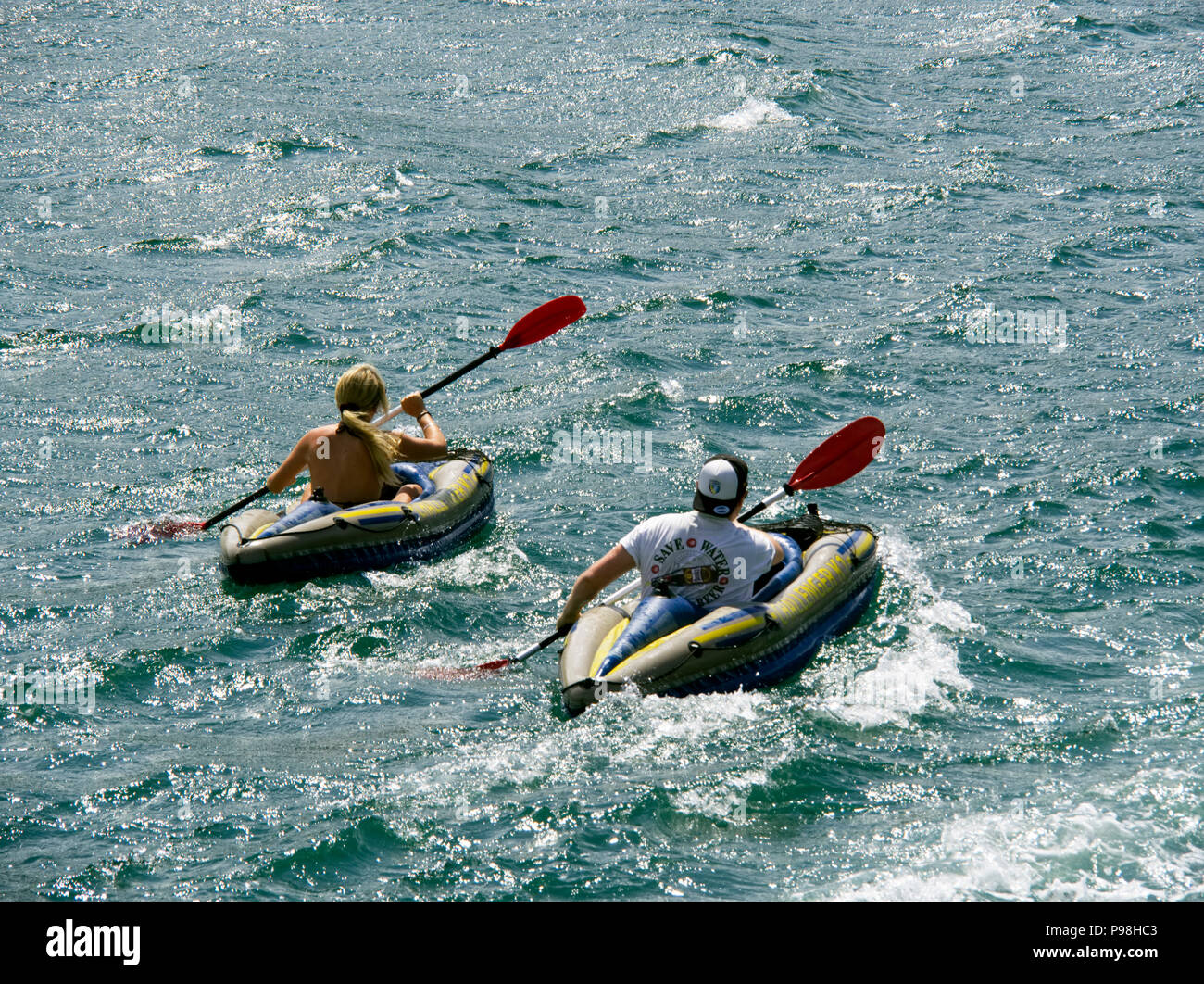 Young male and young female , early 20's enjoying leisure time in inflatable canoes on the clam waters of Salcombe harbour, South Devon, - Stock Image