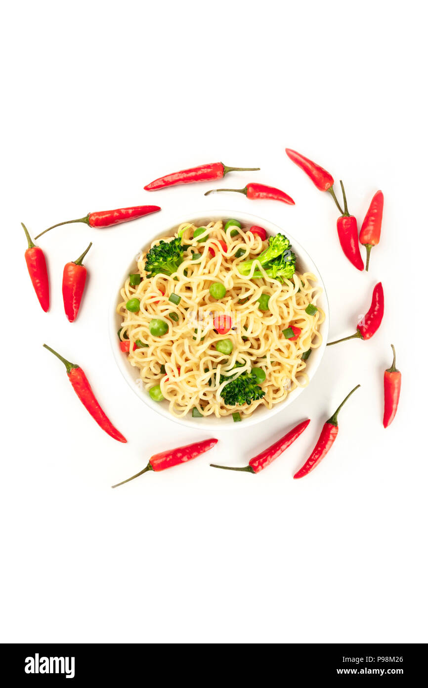 Overhead photo of noodles with vegetables., chili peppers and copy space, on white background - Stock Image