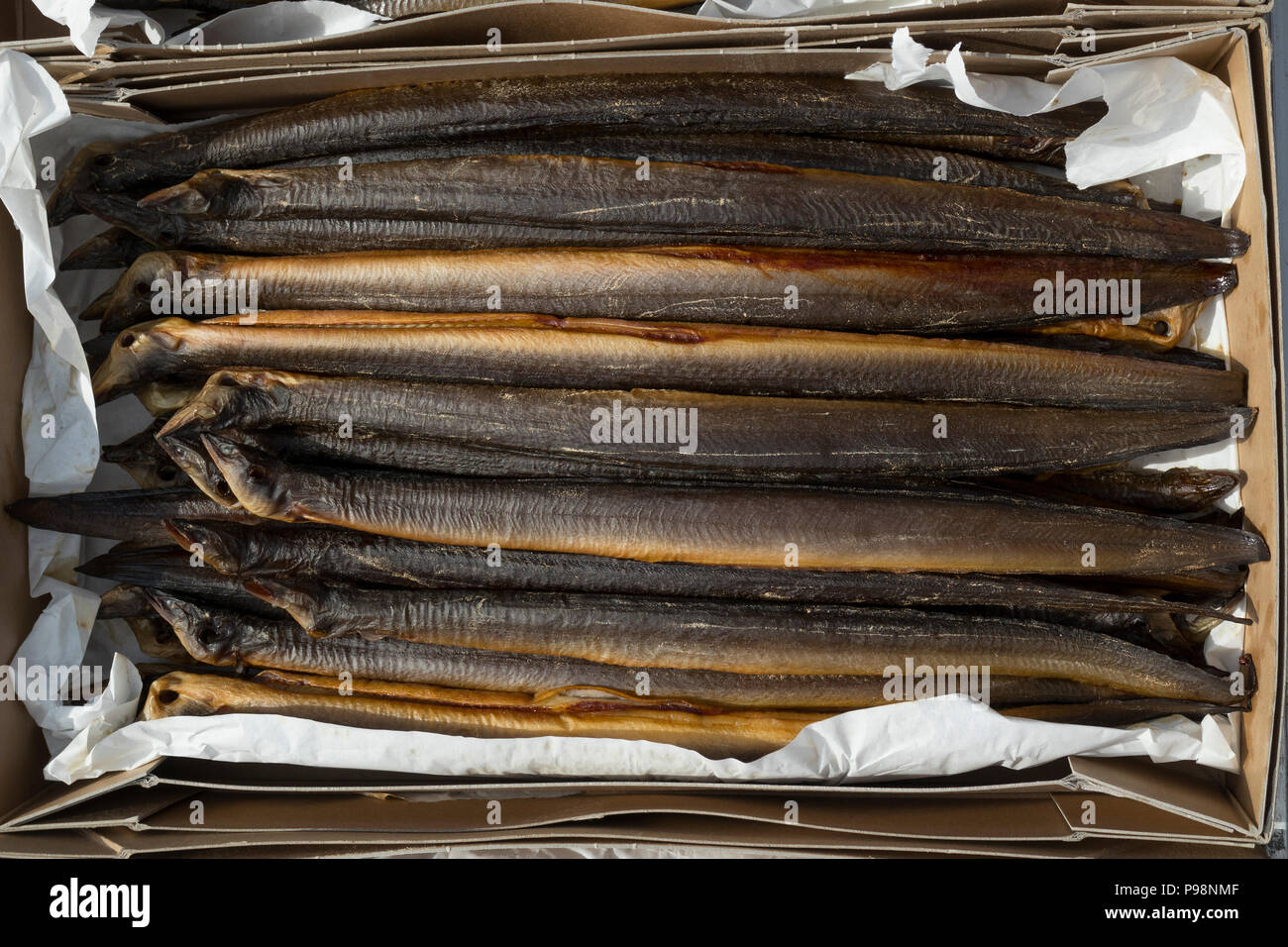Fresh smoked eels in a cardboard box for sale - Stock Image