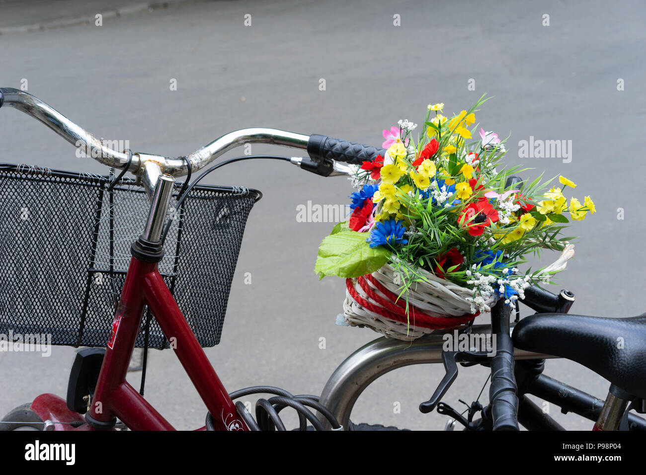 Bicycle with basket of imitation flowers. Poland, Europe. - Stock Image