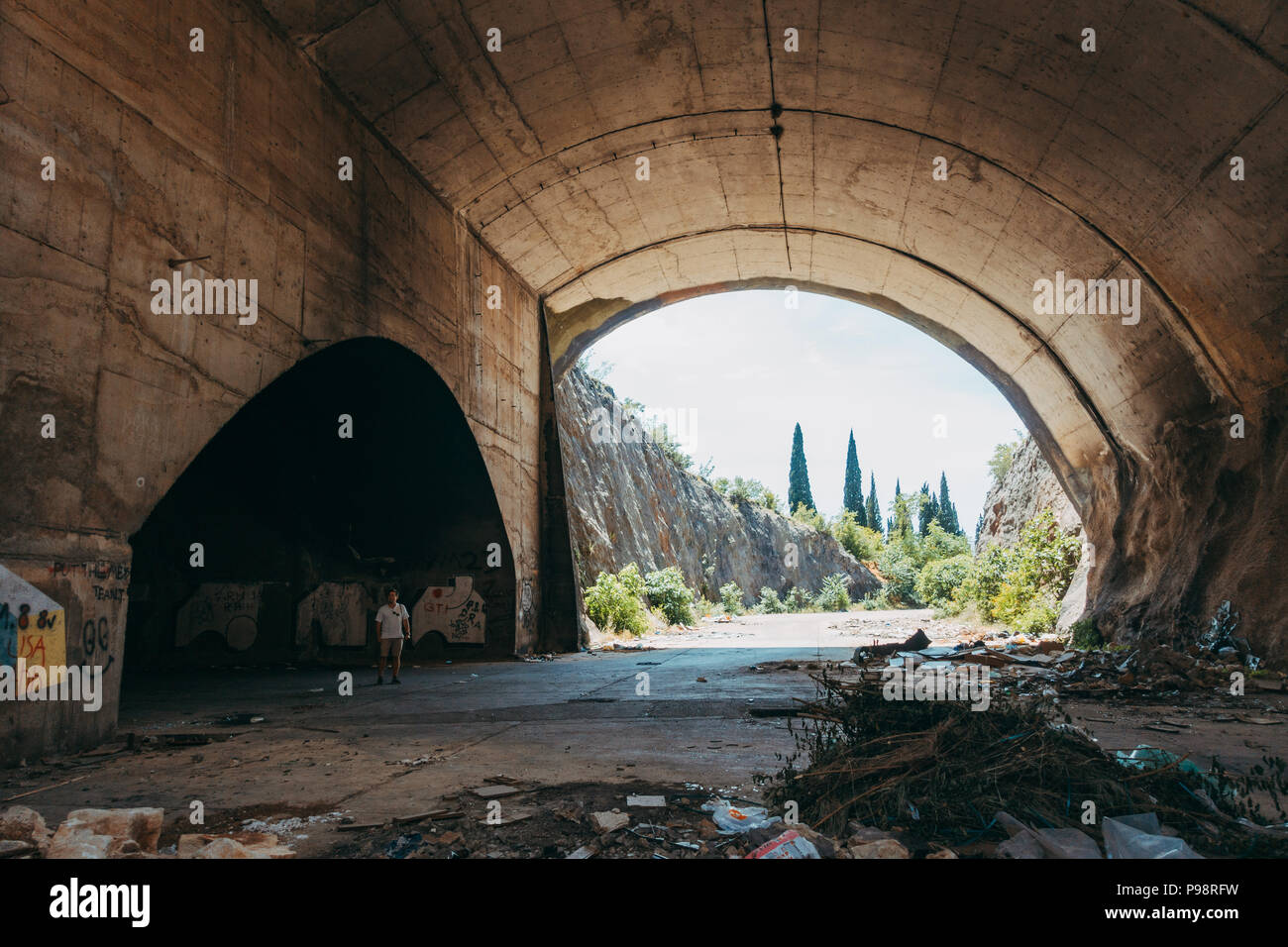 a tourist explores an abandoned aircraft hangar in the mountainside at Mostar Airport, Bosnia and Herzegovina Stock Photo