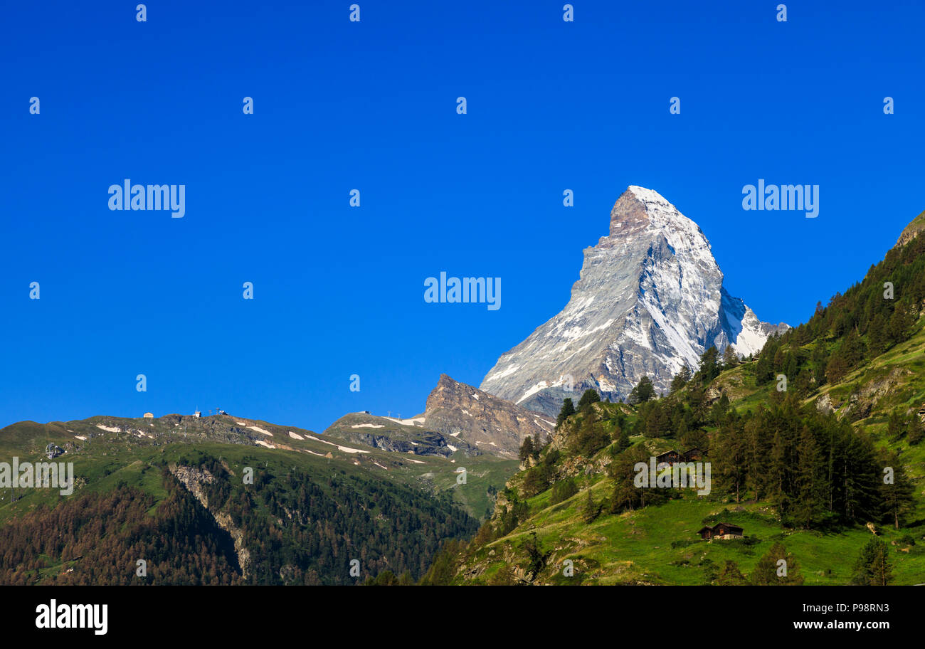 View of the iconic snow-capped peak of the Matterhorn mountain and foothills viewed from Zermatt, Valais, Switzerland with clear blue sky - Stock Image