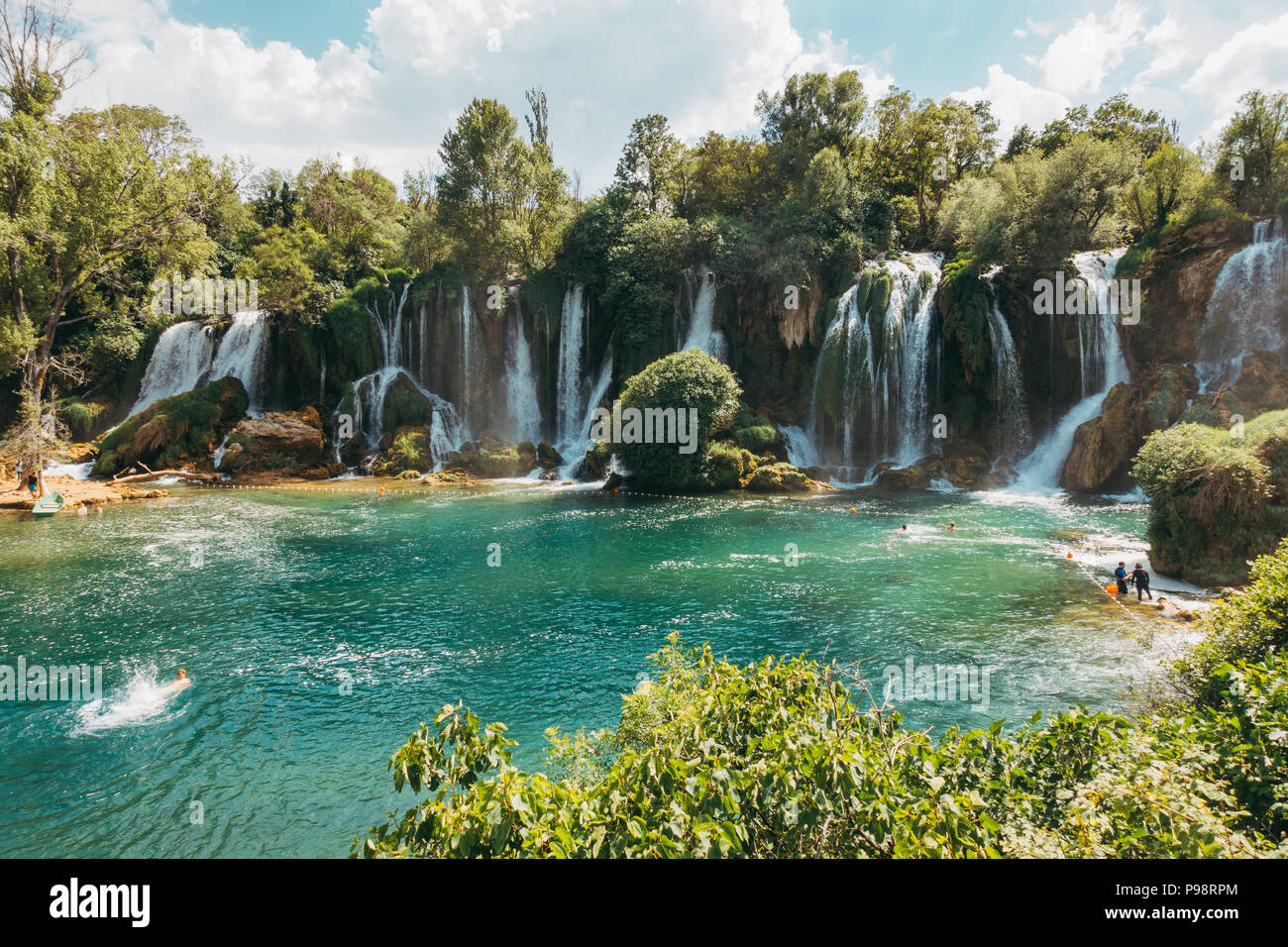 Kravica waterfall - a tufa cascade in Bosnia and Herzegovina, attracts many tourists for a refreshing dip to escape the summer heat - Stock Image