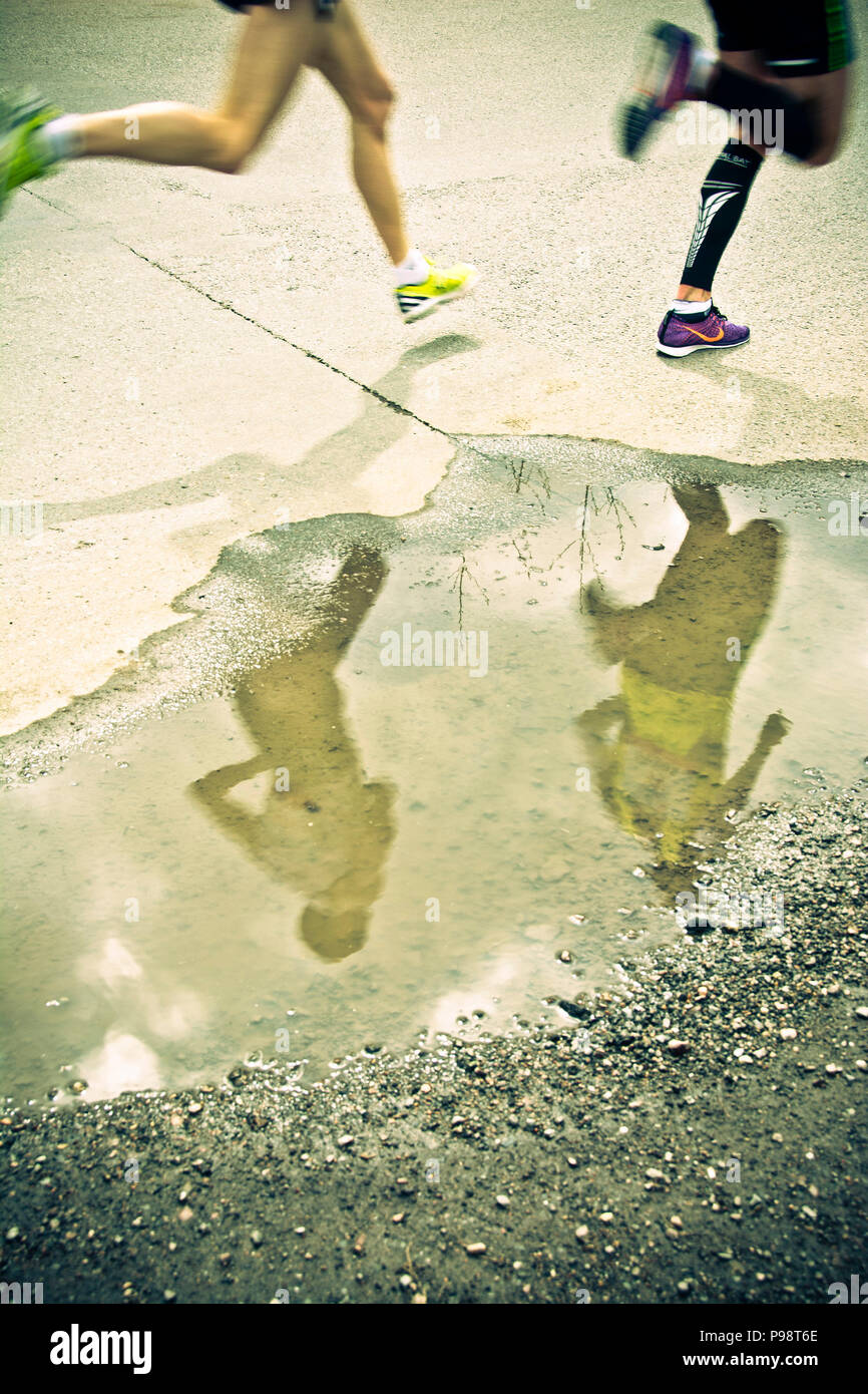 marathon runners legs and reflection in a pool of water - Stock Image