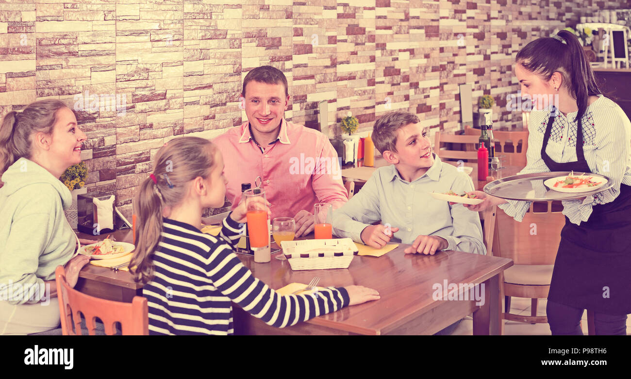 happy brunette waitress serving cheerful family in comfy family cafe - Stock Image