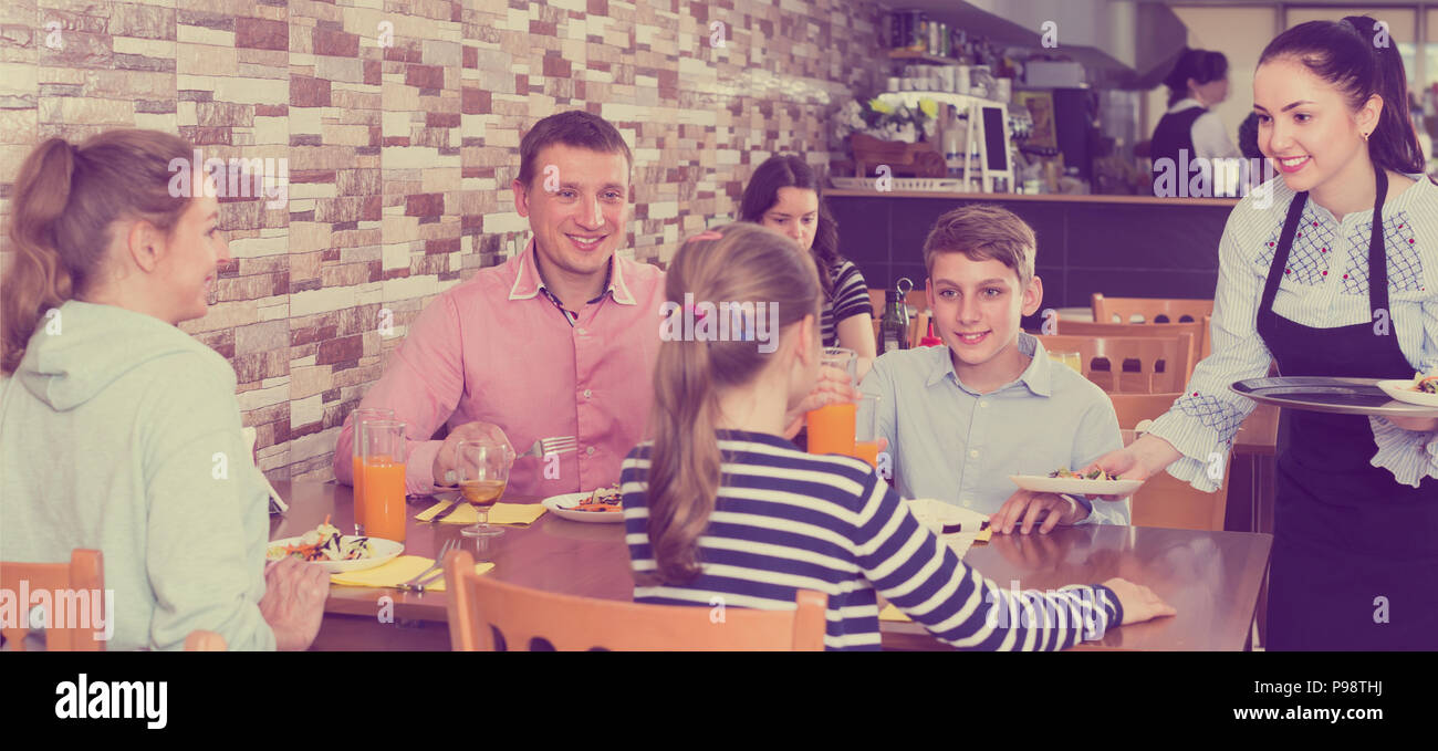 attractive brunette waitress serving cheerful family in comfy family cafe - Stock Image