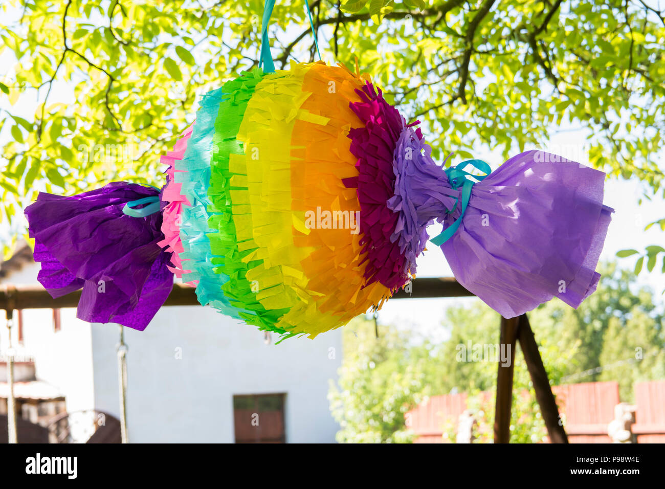 colorfull piniata hanging on the tree - Stock Image