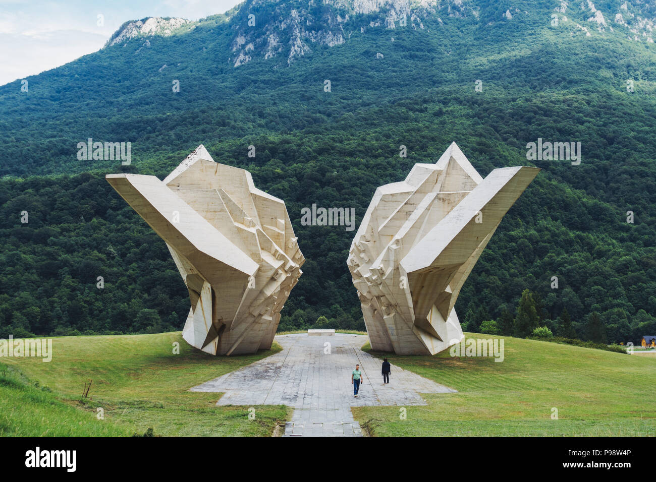 two tourists are dwarfed by the big white Tjentište spomenik (Yugoslav war memorial monument) in the Sutjeska National Park, Bosnia and Herzegovina - Stock Image