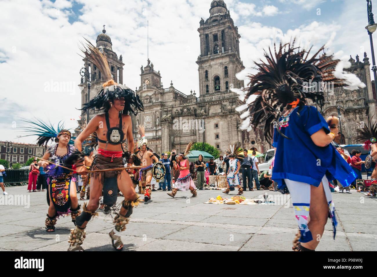 Mexico City, Mexico : Aztec people dancing opposite the Cathedral at the Zócalo square (Plaza de la Constitución) in the historic center of  Mexico Ci Stock Photo