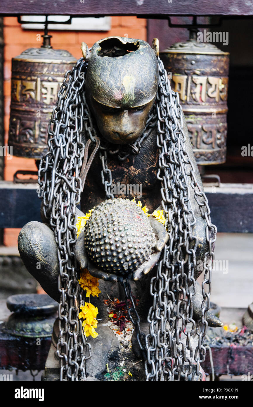 Lalitpur, Kathmandu Valley, Nepal : One out of four monkey statues holding  jackfruit offerings at the courtyard of the Buddhist Golden Temple (aka Kw - Stock Image