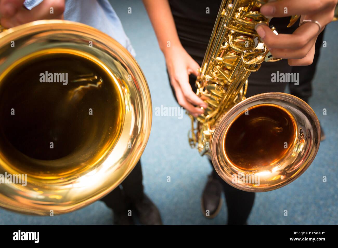 Two secondary aged school children holding saxophones UK - Stock Image