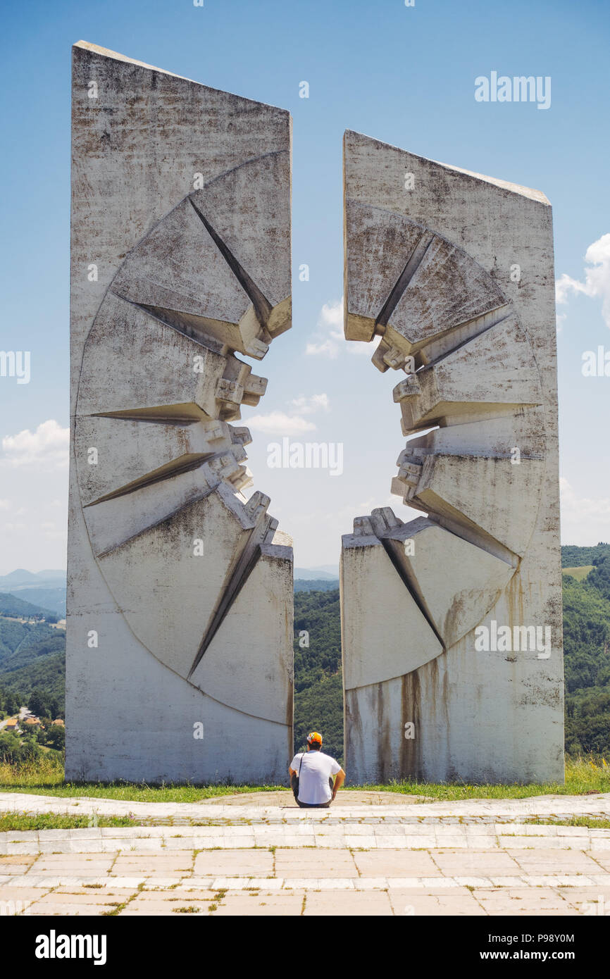a tourist sits in front of a giant white concrete slab at the Kadinjača Memorial Complex, Serbia Stock Photo