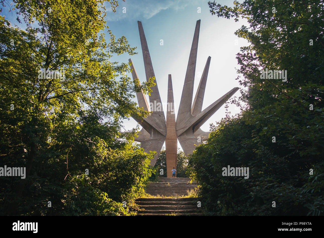 A tourist is dwarfed by the Kosmaj Memorial Complex, a pointy star-like monument erected to the south of Belgrade, Serbia Stock Photo