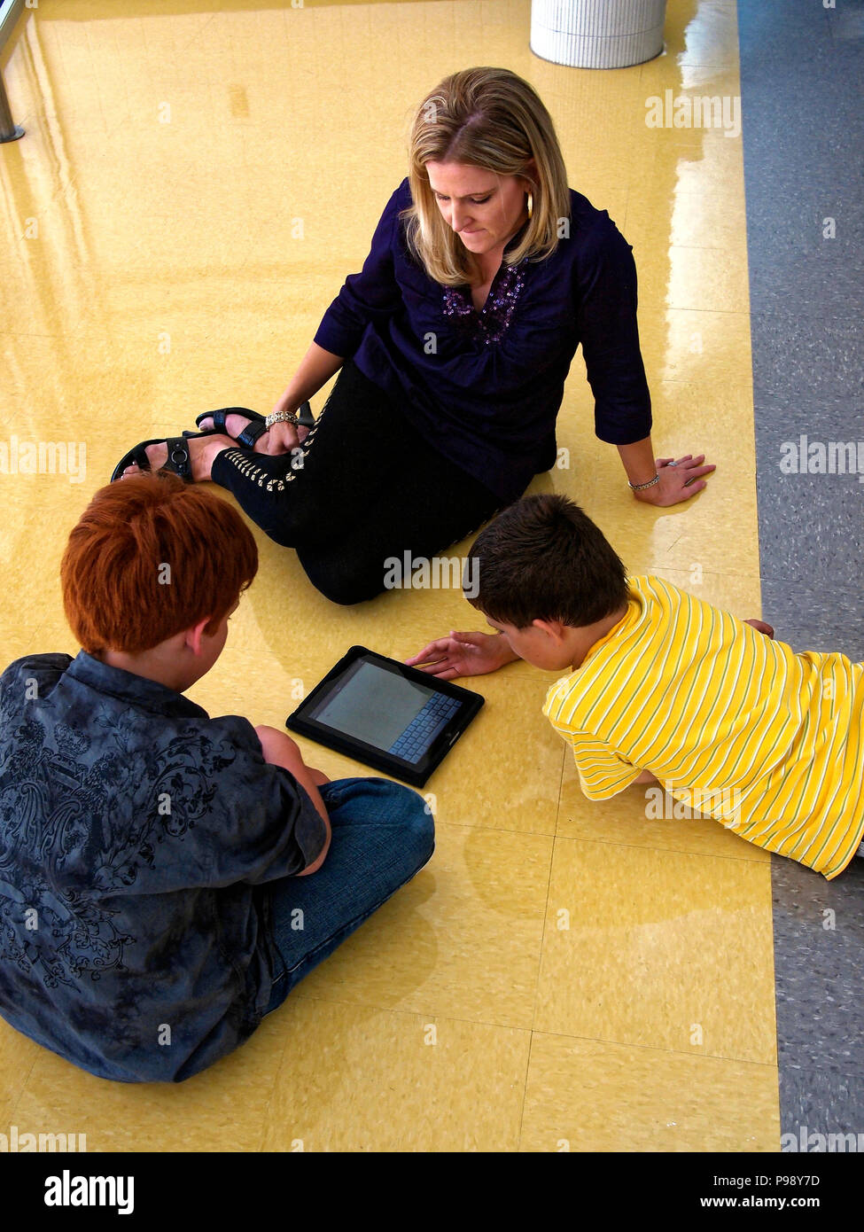 Fifth graders use internet and mobile device like an Apple iPad to research a topic for class. The research then is used for writing a paper on the computer, or making a Powerpoint presentation. Al to get a good grade in school - Stock Image